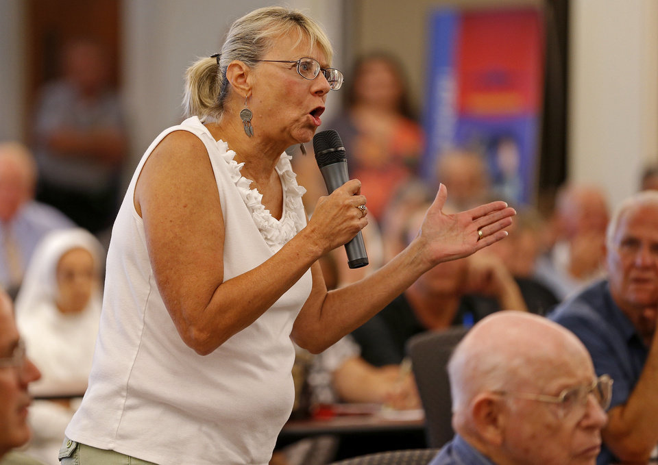 Photo - Cheryl Cooper, of Oklahoma City, asks Rep. Tom Cole, R-Moore, a question during a town hall meeting at Rose State College in Midwest City, Tuesday, September 3, 2013. Photo by Bryan Terry, The Oklahoman  BRYAN TERRY - THE OKLAHOMAN