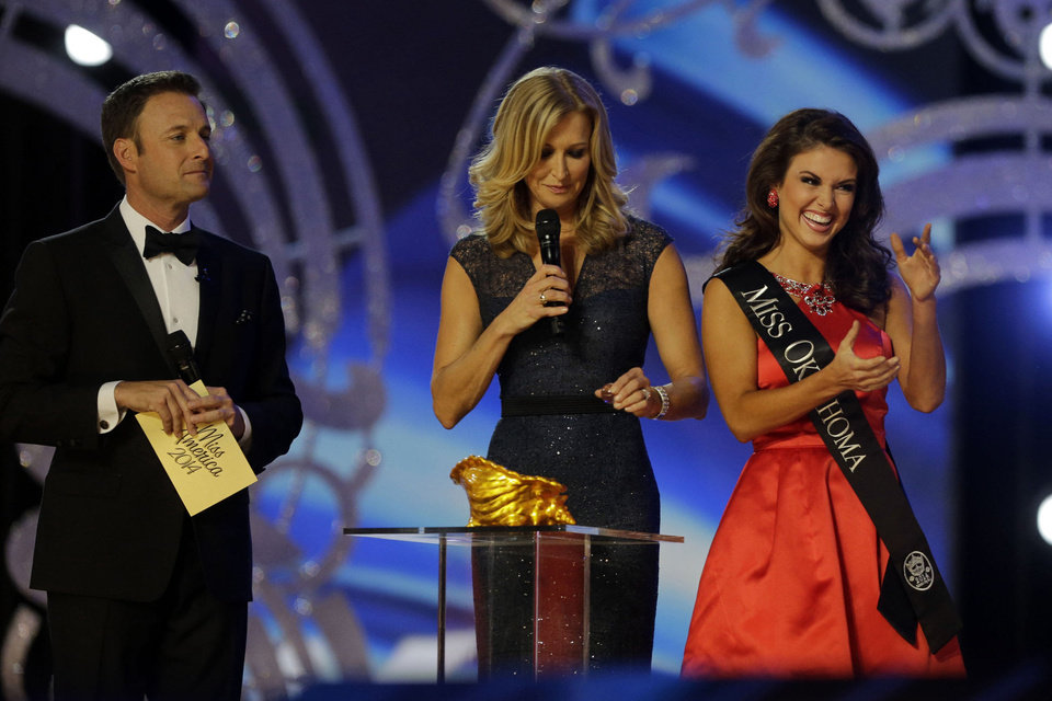 Photo - Miss Oklahoma Kelsey Griswold, right, reacts before answering a question during the Miss America 2014 pageant, Sunday, Sept. 15, 2013, in Atlantic City, N.J. (AP Photo/Mel Evans)