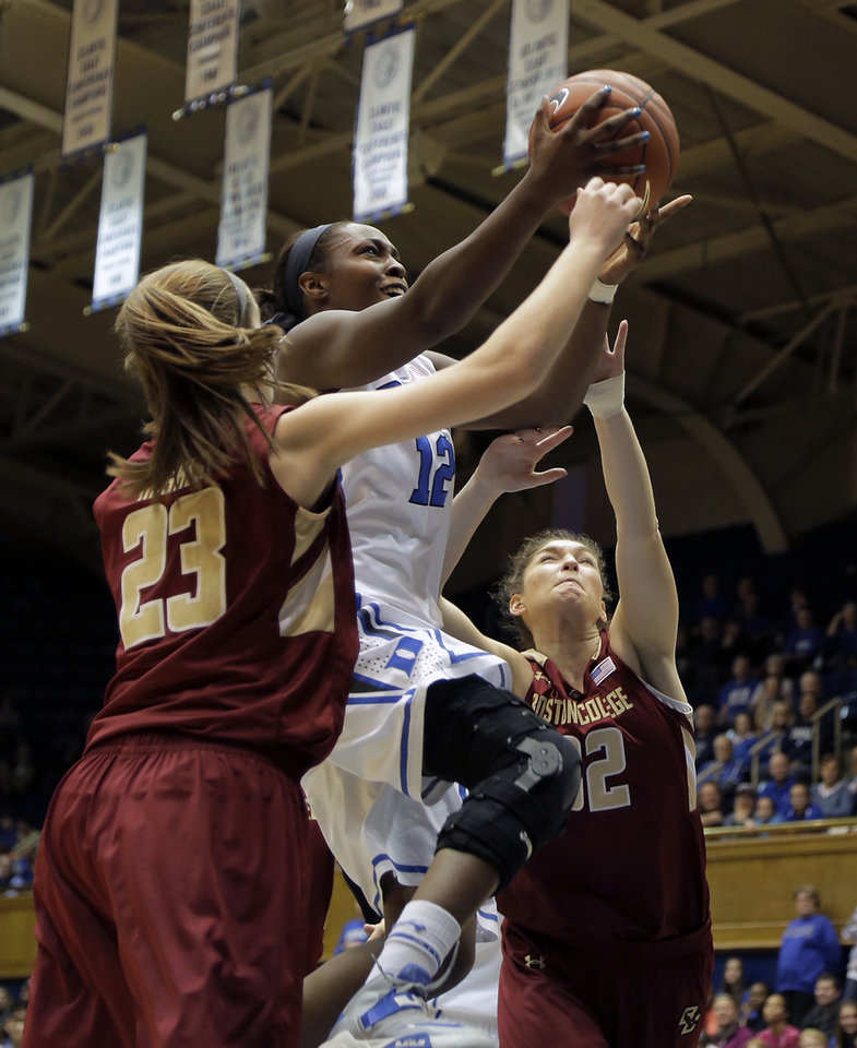 Photo - Duke's Chelsea Gray (12) drives to the basket between Boston College's Kelly Hughes (23) and Victoria Lesko, right, during the first half of an NCAA college basketball game in Durham, N.C., Sunday, Jan. 12, 2014. (AP Photo/Ted Richardson)