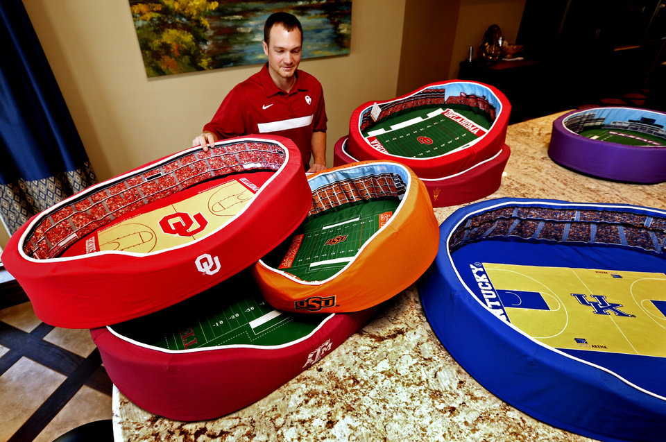 Photo - Kevin Kruger shows pet beds Thursday that he designed and sells that look like college sports stadiums.  Photos by Steve Sisney, The Oklahoman   STEVE SISNEY - THE OKLAHOMAN