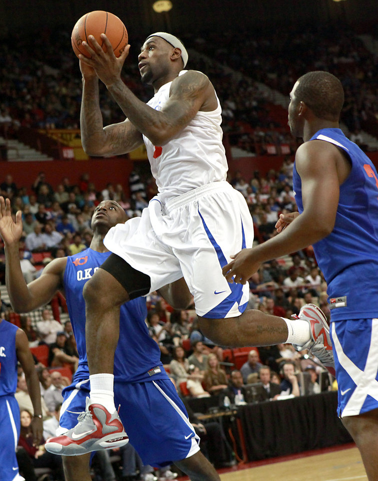 Photo - LeBron James puts up a shot in front of Damien Wilkins (left) and Chris Paul during the US Fleet Tracking Basketball Invitational at the Cox Convention Center in Oklahoma City Sunday, Oct. 23, 2011. The White Team defeated the Blue Team 176-171. Photo by John Clanton, The Oklahoman