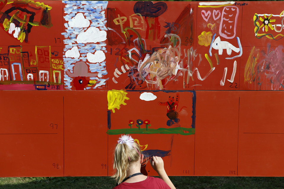 Photo - Delaney Barber, 12, paints on the children's art wall during the Midsummer Nights' Fair in Norman on Saturday. Photos by Bryan Terry, The Oklahoman