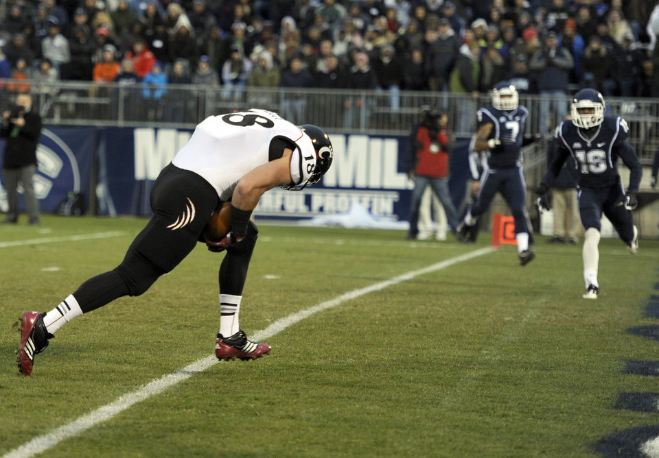 Photo - Cincinnati tight end Travis Kelce, left, crosses the goal line for a touchdown during the first half of an NCAA college football game against Connecticut at Rentschler Field in East Hartford, Conn., Saturday, Dec. 1, 2012. (AP Photo/Jessica Hill)