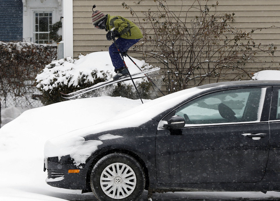 Photo - Milo Bloom, 10, skis over a snowbank next to a parked car during a snowstorm, Thursday, Jan. 2, 2014, in Portland, Maine. Strong winds are creating blizzard-like conditions. A wind chill factor of 30 degrees below zero is expected Friday. (AP Photo/Robert F. Bukaty)