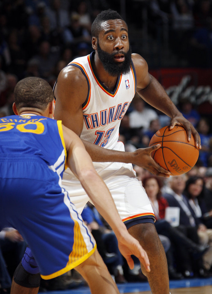 Photo - Oklahoma City's James Harden (13) looks to pass around Golden State's Stephen Curry (30) during the NBA basketball game between the Oklahoma City Thunder and the Golden State Warriors at the Chesapeake Energy Arena in Oklahoma City, Friday, Feb. 17, 2012. Photo by Nate Billings, The Oklahoman