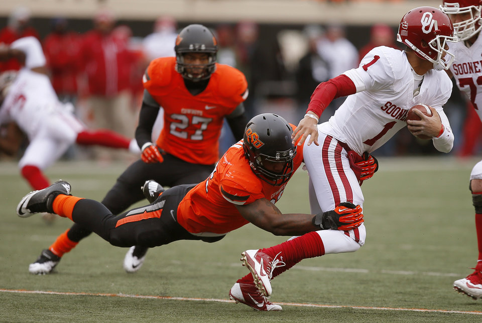 Photo - Oklahoma's Kendal Thompson (1) tries to get away from Oklahoma State's Jimmy Bean (92) during the Bedlam college football game between the Oklahoma State University Cowboys (OSU) and the University of Oklahoma Sooners (OU) at Boone Pickens Stadium in Stillwater, Okla., Saturday, Dec. 7, 2013. Oklahoma won 33-24. Photo by Bryan Terry, The Oklahoman
