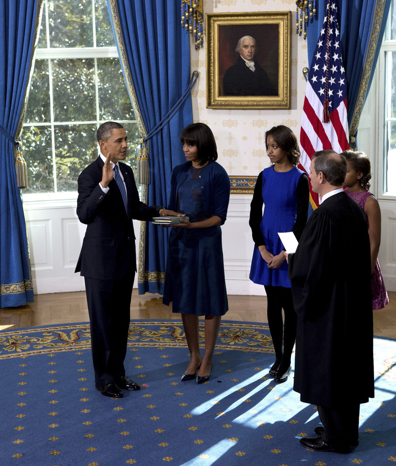 Photo - President Barack Obama is officially sworn-in by Chief Justice John Roberts, not pictured, in the Blue Room of the White House during the 57th Presidential Inauguration in Washington, Sunday Jan. 20, 2013, as first lady Michelle Obama, holds the Robinson Family Bible, as daughter Malia and Sasha watch. (AP Photo/The New York Times, Doug Mills, Pool) ORG XMIT: NYNYT303