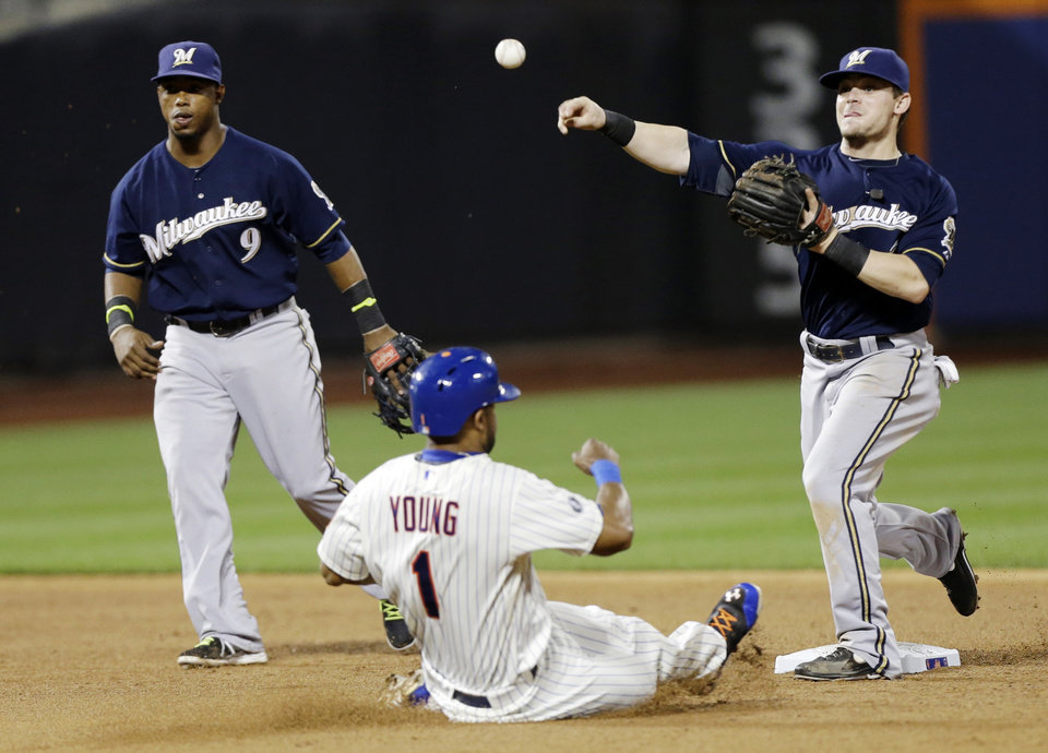Photo - Milwaukee Brewers second baseman Scooter Gennett, right, throws out New York Mets' Taylor Teagarden at first base after forcing out Chris Young (1) for a double play as teammate Jean Segura (9) watches during the eighth inning of a baseball game Tuesday, June 10, 2014, in New York. (AP Photo/Frank Franklin II)