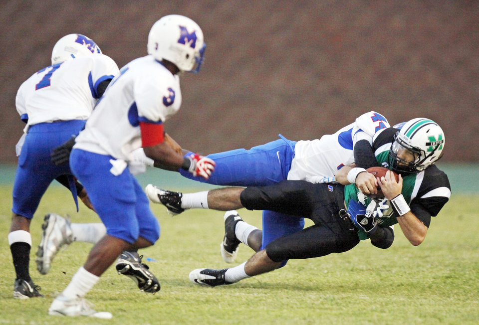Millwood's Larry Lambeth takes down Bishop McGuinness' Camden Tharp, bottom right, next to Malcom Scales, left, and Cameron Batson during a Sept. 16 game at Pribil Stadium.  Photo by Nate Billings, The Oklahoman