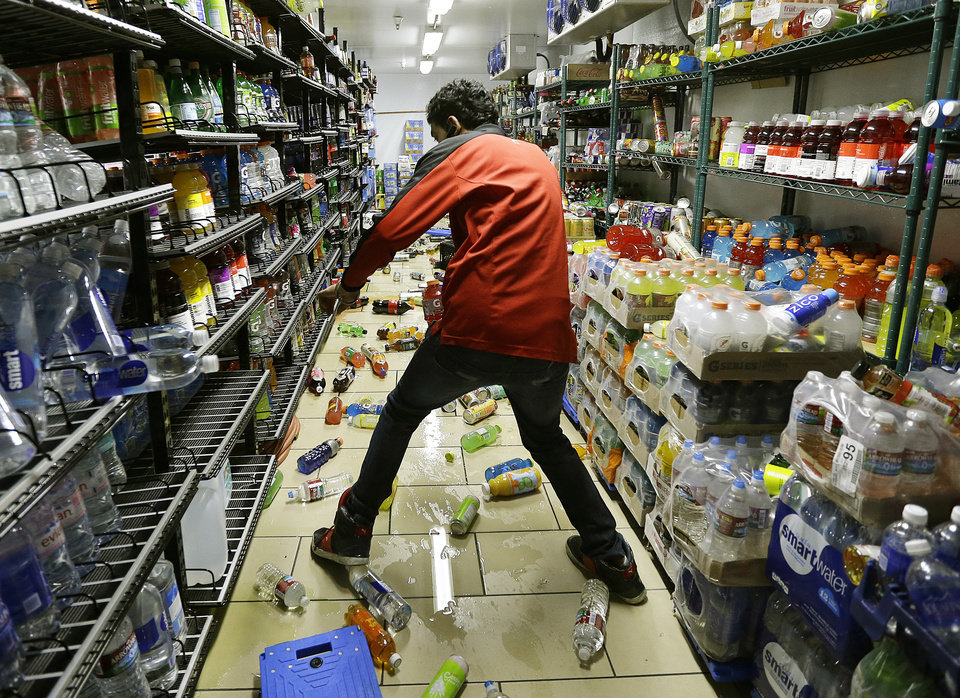 Photo - Gurbeer Singh cleans up merchandise which fell due to an earthquake at a 7-Eleven store Sunday, Aug. 24, 2014, in American Canyon, Calif. Officials say an earthquake with a preliminary magnitude of 6.0 has been reported in California's northern San Francisco Bay area. (AP Photo/Ben Margot)
