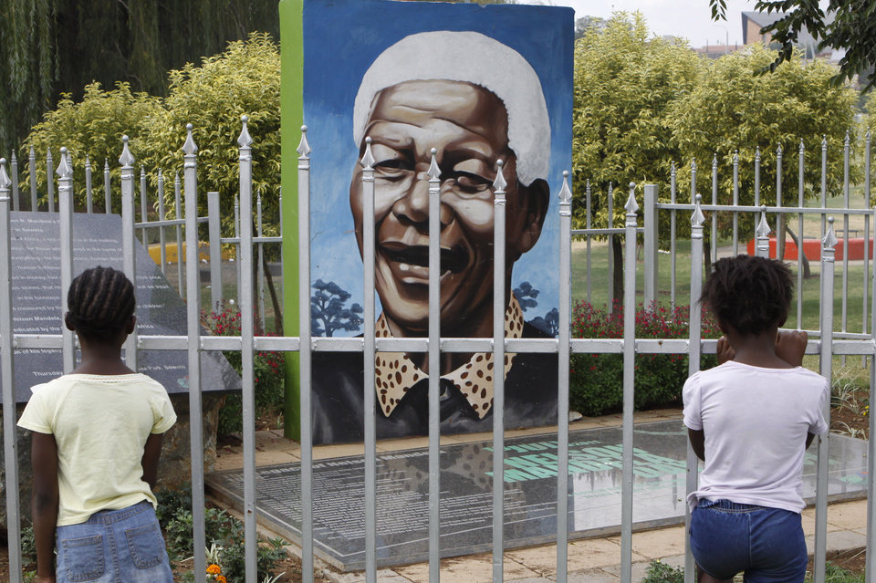 Photo - Children look through a fence at a portrait of former president Nelson Mandela in a Park in Soweto, South Africa, Thursday, March, 28, 2013. 94-year-old Mandela, the anti-apartheid leader who became South Africa's first black president, has been hit by a lung infection again and is in a hospital, the presidency said. Mandela, has become increasingly frail in recent years and has been hospitalized several times in recent months, including earlier this month when he underwent what authorities said was a scheduled medical test. The Nobel laureate is a revered figure in South Africa, which has honored his legacy of reconciliation by naming buildings and other places after him and printing his image on national banknotes. (AP Photo/Denis Farrell)