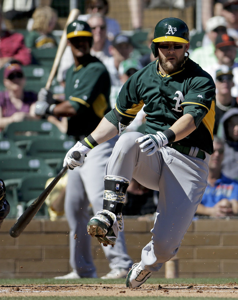 Photo - Oakland Athletics first baseman Daric Barton falls after a strike during the first inning of a spring training baseball game against the Colorado Rockies in Scottsdale, Ariz., Saturday, March 8, 2014. (AP Photo/Chris Carlson)