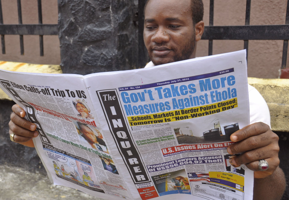 Photo - A man reads a newspaper with headlines reading 'Gov't Takes More Measures Against Ebola, as fear about the virus spread in the city of Monrovia, Liberia, Thursday, July 31, 2014. The worst recorded Ebola outbreak in history surpassed 700 deaths in West Africa as the World Health Organization on Thursday announced dozens of new fatalities. (AP Photo/Abbas Dulleh)