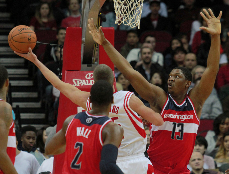 Photo - Washington Wizards center Kevin Serphin (13) defends as Houston Rockets forward Chandler Parsons, center, goes up to shoot and Wizards' John Wall looks on during the first half of an NBA basketball game in Houston, Wednesday, Feb. 12, 2014. (AP Photo/Richard Carson)