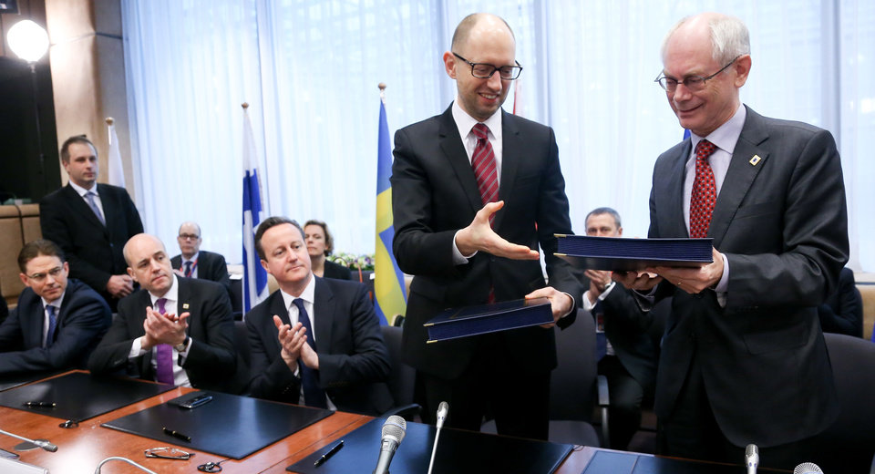 Photo - Ukrainian Prime Minister Arseniy Yatsenyuk, second right, and European Council President Herman Van Rompuy, right, hand each other their books during a signing ceremony at an EU summit in Brussels on Friday, March 21, 2014. Ukraine's prime minister has pulled his nation closer into Europe's orbit, signing a political association agreement with the EU at a summit of the bloc's leaders. Friday's agreement between Prime Minister Arseniy Yatsenyuk and the EU leaders was part of the pact that former President Viktor Yanukovych backed out of last November in favor of a $15 billion bailout from Russia. That decision sparked the protests that ultimately led to his downfall and flight last month, setting off  one of Europe's worst political crises since the Cold War. From left, Finnish Prime Minister Jyrki Katainen, Swedish Prime Minister Fredrik Reinfeldt and British Prime Minister David Cameron. (AP Photo/Olivier Hoslet, Pool)