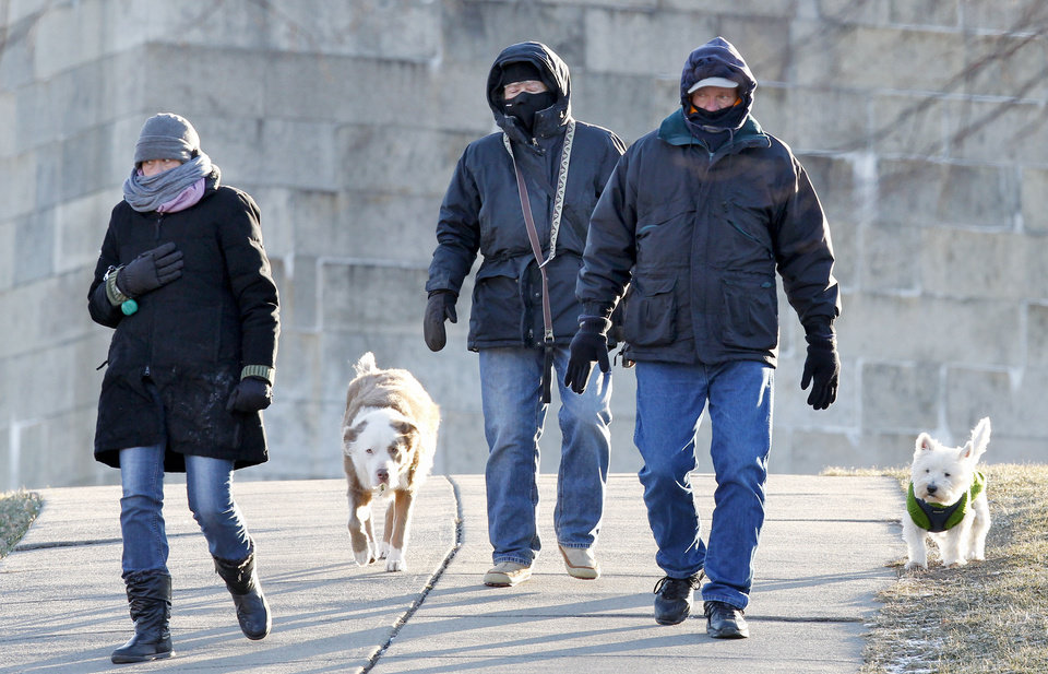 South Boston residents who did not wish to be identified walk their dogs at Castle Island in Boston, Wednesday, Jan. 23, 2013. The National Weather Service says it\'s not expected to get above 17 degrees in Boston, with the wind chill making it feel five below. (AP Photo/Michael Dwyer)