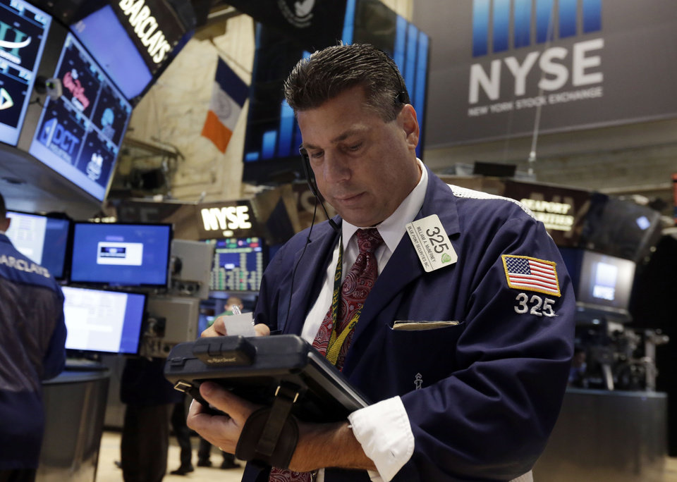 Photo - Trader William McInerney works on the floor of the New York Stock Exchange Tuesday, July 1, 2014. The stock market rose in early trading after a report showed that manufacturing in the US and China expanded in June, boosting the outlook for global growth. (AP Photo/Richard Drew)