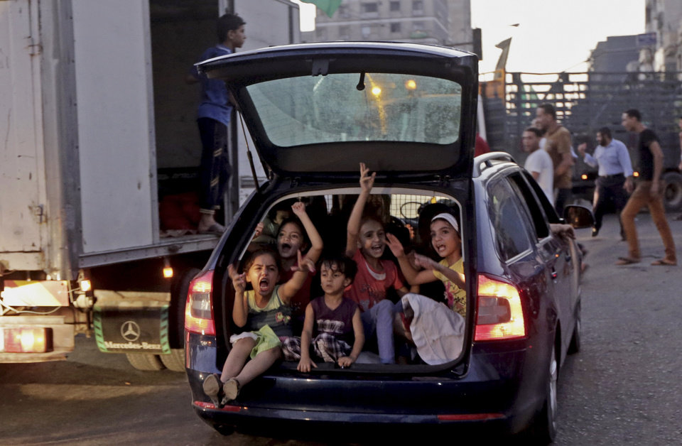 Photo - Palestinian children sit inside the trunk of their family car while chanting slogans as they celebrate the cease-fire between Palestinians and Israelis at the main rood in Gaza, in the northern Gaza Strip, Tuesday, Aug. 26, 2014.  Israel and Hamas agreed Tuesday to an open-ended cease-fire, halting a seven-week war that killed more than 2,200 people, the vast majority Palestinians, left tens of thousands in Gaza homeless and devastated entire neighborhoods in the blockaded territory.  (AP Photo/Adel Hana)