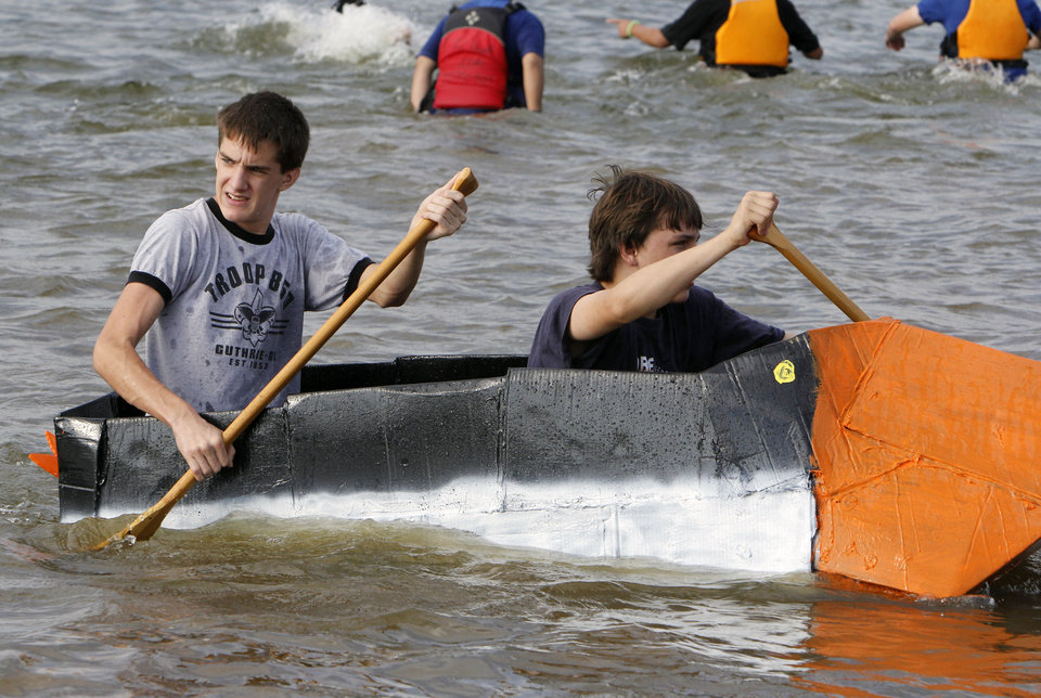 "Boy Scout Troop 850 members Harlan McGuire, left, and Claxton Hymel come in third place in their boat ""Armadillo"" during the Fourth Annual Cardboard Boat Regatta at Arcadia Lake in Edmond, OK, Saturday, August 25, 2012.  By Paul Hellstern, The Oklahoman"