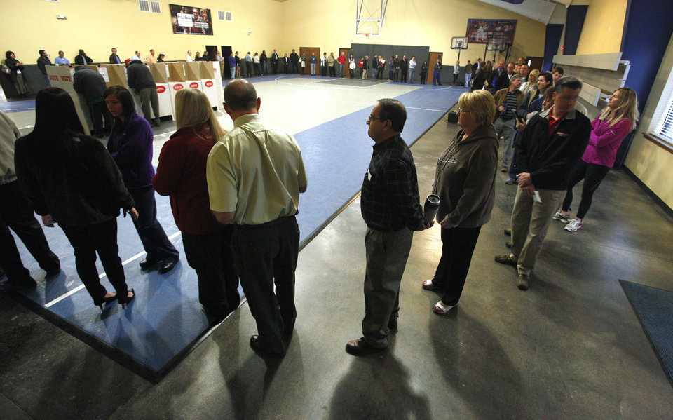 Photo - The line of people snakes along the gymnasium walls as voting starts at 7 am at precinct 137 in Oklahoma City Tuesday, Nov. 6, 2012.  Photo by Paul B. Southerland, The Oklahoman