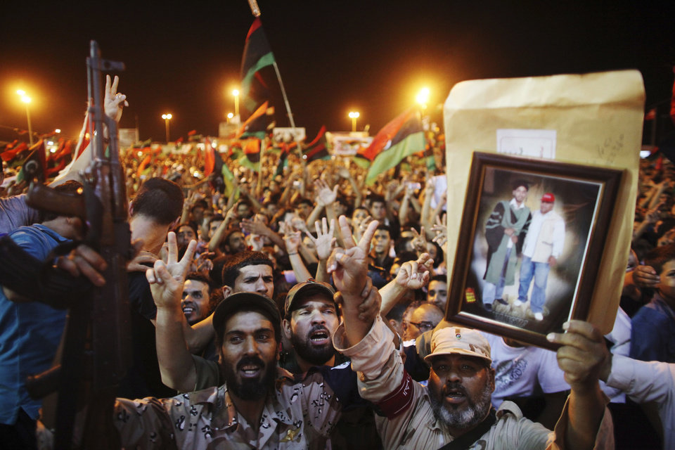 Photo -   People celebrate the capture in Tripoli of Moammar Gadhafi's son and one-time heir apparent, Seif al-Islam, at the rebel-held town of Benghazi, Libya, early Monday, Aug. 22, 2011. Libyan rebels raced into Tripoli Sunday and met little resistance as Gadhafi's defenders melted away and his 42-year rule rapidly crumbled. (AP Photo/Alexandre Meneghini)