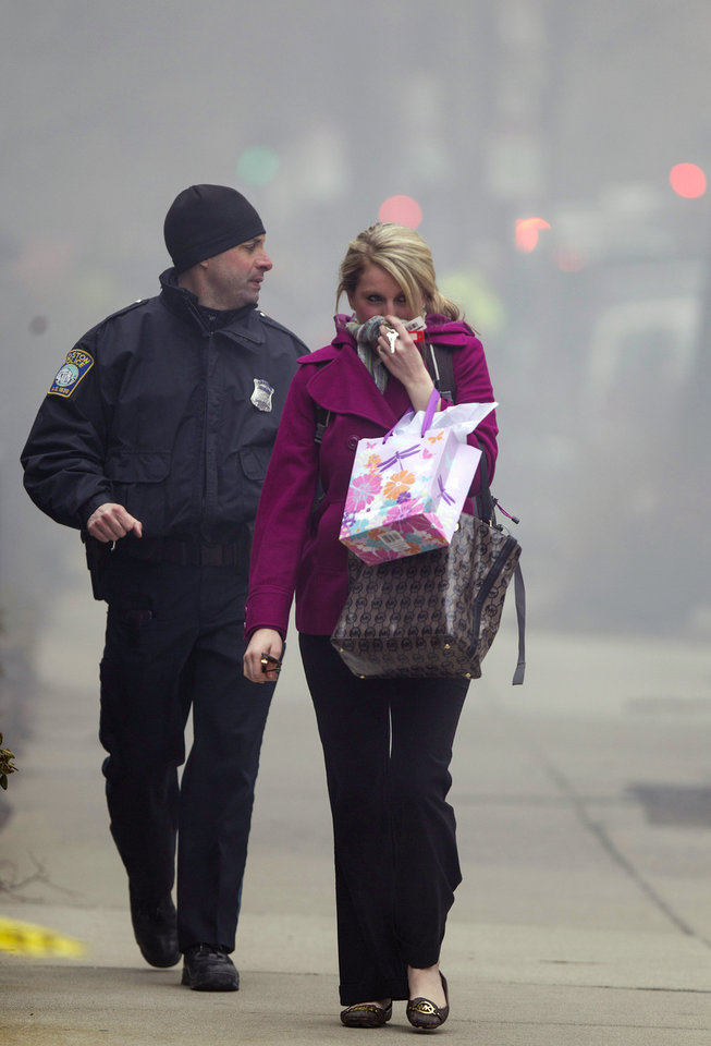 Photo - A Boston Police officer escorts a woman away from the scene of a multi-alarm fire at a four-story brownstone in the Back Bay neighborhood near the Charles River, Wednesday, March 26, 2014, in Boston. Boston EMS spokesman Nick Martin says four people, including at least three firefighters, have been taken to hospitals. (AP Photo/Scott Eisen)