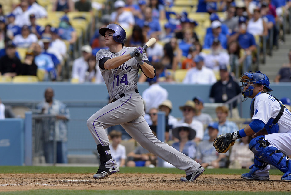 Colorado Rockies' Josh Rutledge, left, hits a three-run home run as Los Angeles Dodgers catcher Tim Federowicz looks on during the sixth inning of a baseball game, Sunday, April 27, 2014, in Los Angeles. (AP Photo/Mark J. Terrill)