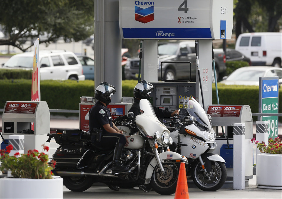 Photo - In this Thursday, Apr. 25, 2013, photo, Los Angeles Police police officers fill up at a Chevron gas station downtown Los Angeles. Chevron Corp. reports quarterly financial results before the market opens on Friday, April 26, 2013. (AP Photo/Damian Dovarganes)