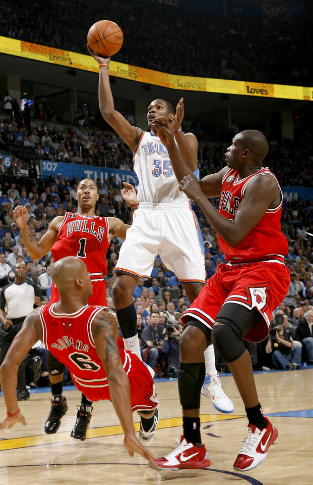 Photo - Oklahoma CIty's Kevin Durant goes between Chicago's Derrick Rose, left, Keith Bogans, and Luol Deng during the NBA basketball game between the Oklahoma City Thunder and the Chicago Bulls in the Oklahoma City Arena on Wednesday, Oct. 27, 2010. Photo by Bryan Terry, The Oklahoman