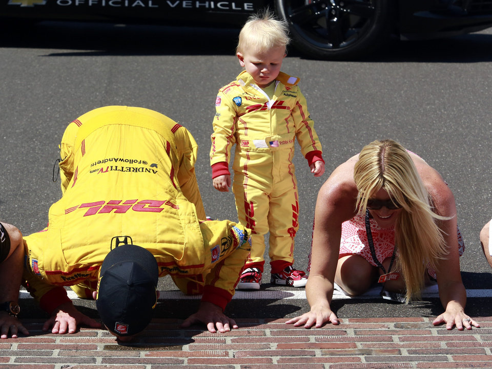 Photo - Ryan Hunter-Reay and his wife, Beccy Gordon, kiss the bricks as their son, Ryden, watches after Hunter-Reay won during the 98th running of the Indianapolis 500 IndyCar auto race at the Indianapolis Motor Speedway in Indianapolis, Sunday, May 25, 2014. (AP Photo/R Brent Smith)