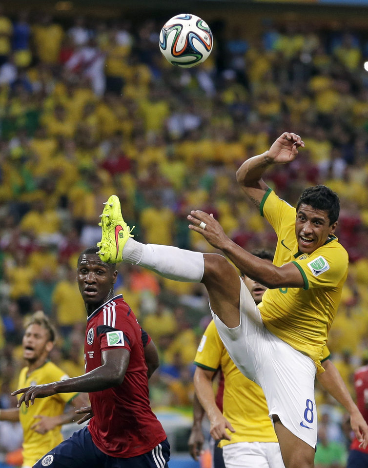 Photo - Brazil's Paulinho, right, challenges Colombia's Cristian Zapata during the World Cup quarterfinal soccer match between Brazil and Colombia at the Arena Castelao in Fortaleza, Brazil, Friday, July 4, 2014. (AP Photo/Felipe Dana)