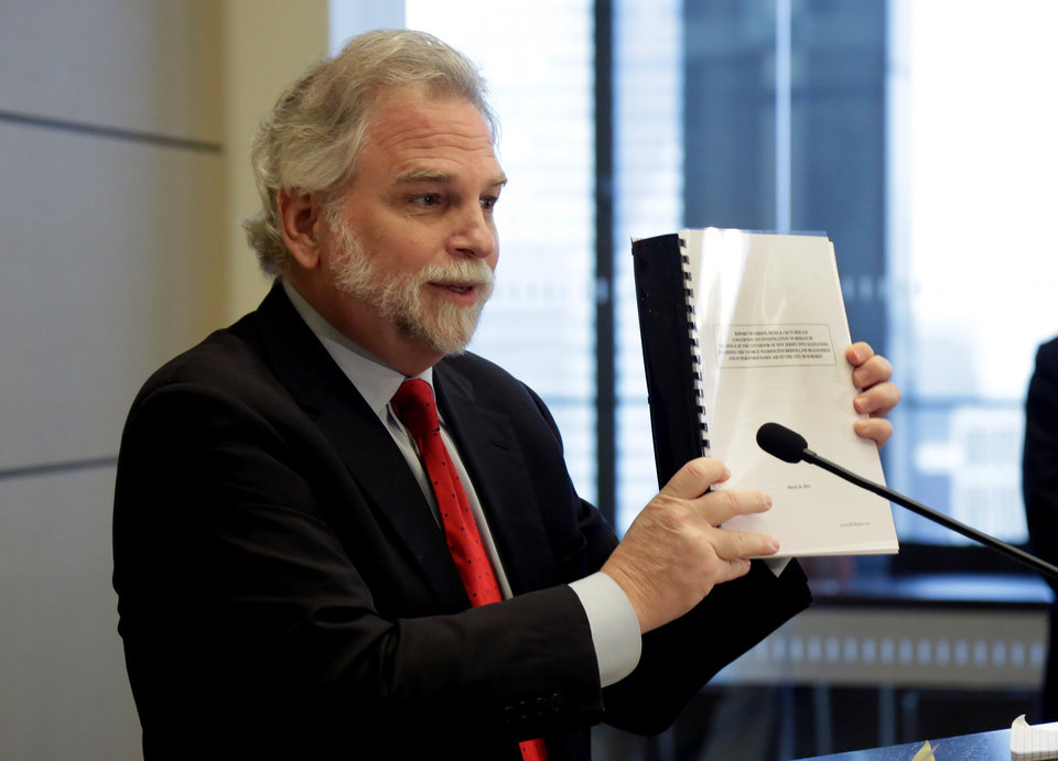 Photo - Attorney Randy Mastro holds up a copy of his report during a news conference Thursday, March 27, 2014, in New York.  Mastro, with the law firm hired by New Jersey Gov. Chris Christie, said Thursday that the governor was not involved in a plot to create gridlock near a major bridge as part of a political retribution scheme. (AP Photo/Richard Drew)