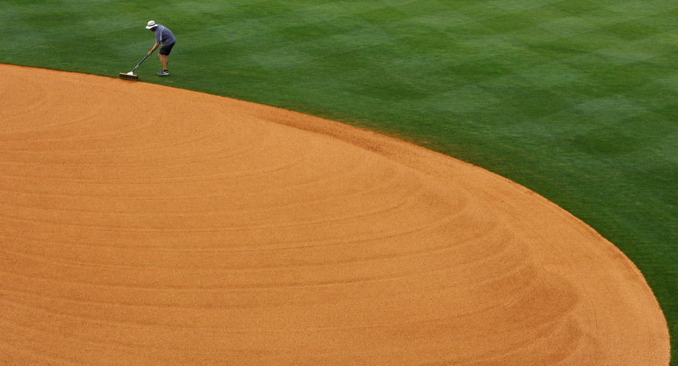 Photo - In this May 24, 2014 photo, a ground crew member sweeps the dirt back onto the infield at the Southeastern Conference NCAA college baseball tournament in Hoover, Ala. (AP Photo/Butch Dill)