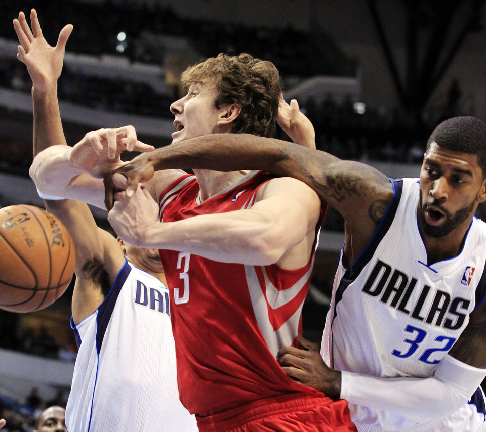 Houston Rockets center Omer Asik (3) is pressured under the basket by Dallas Mavericks center Chris Kaman, left, and guard O.J. Mayo (32) during the first half of an NBA basketball game, Wednesday, Jan. 16, 2013, in Dallas. (AP Photo/John F. Rhodes)