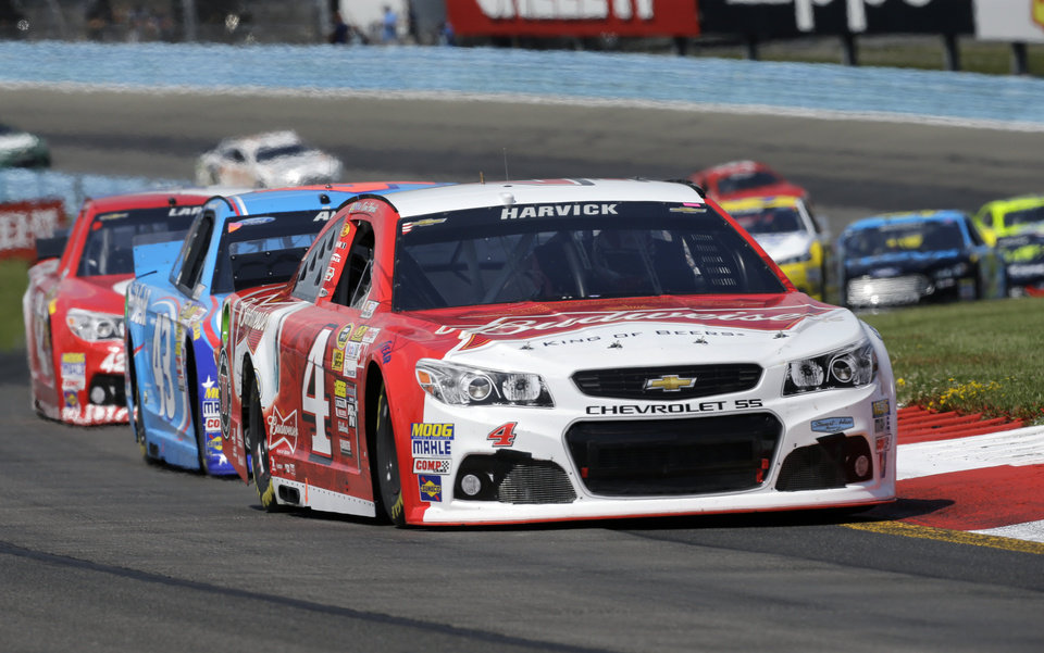 Photo - Kevin Harvick (4) leads a group of racers through the esses during a NASCAR Sprint Cup Series auto race at Watkins Glen International, Sunday, Aug. 10, 2014, in Watkins Glen N.Y. (AP Photo/Mel Evans)
