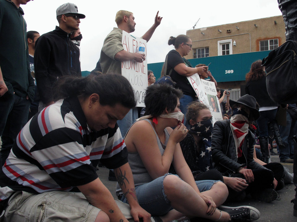 Photo - FILE- In this March 30, 2014 file photo, protesters sit during a rally against recent police shootings in Albuquerque, N.M. As Albuquerque continues to see public demonstrations over a rash of police shootings, activists said they are looking to New Mexico's history of resistance and previous protests to draw attention to what they said are major problems within the police department. (AP Photo/Russell Contreras)