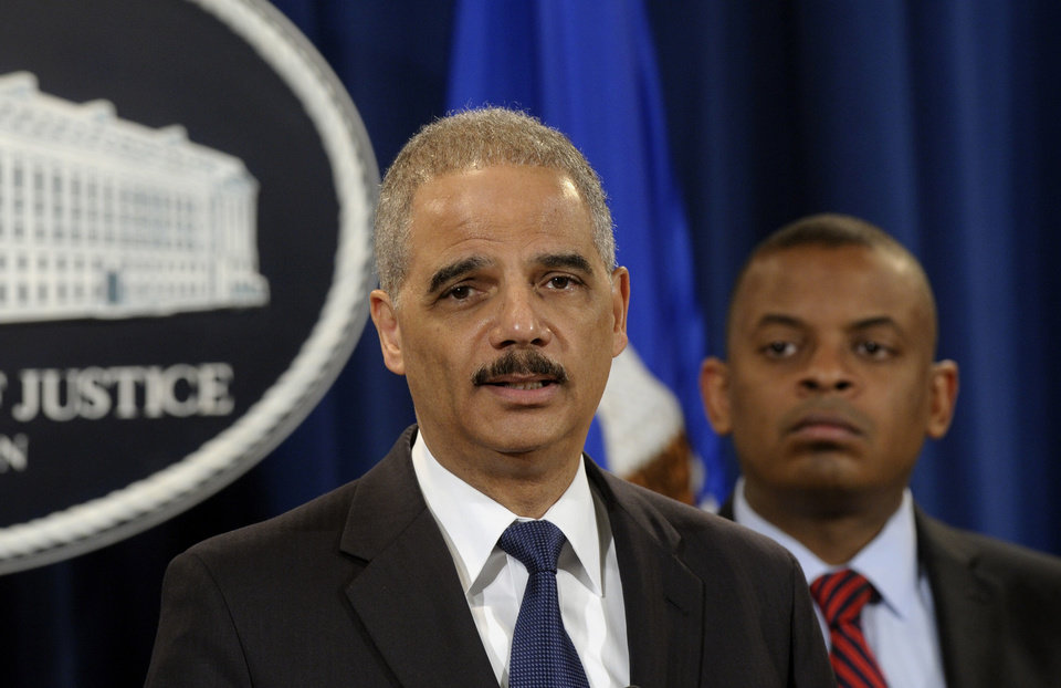 Photo - Attorney General Eric Holder, left, accompanied byTransportation Secretary Anthony Foxx, announces a $1.2 billion settlement with Toyota over its disclosure of safety problems, Wednesday, March 19, 2014, during a news conference at the Justice Department in Washington. (AP Photo/Susan Walsh)