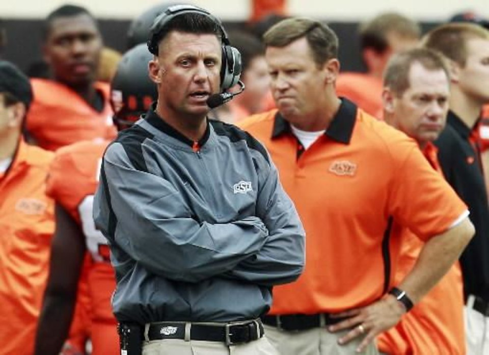 Oklahoma State head coach Mike Gundy talks on his headset as he watches from the sidelines in the fourth quarter of an NCAA college football game against Louisiana-Lafayette in Stillwater, Okla., Saturday, Sept. 15, 2012. Oklahoma State won 65-24. (AP Photo/Sue Ogrocki)