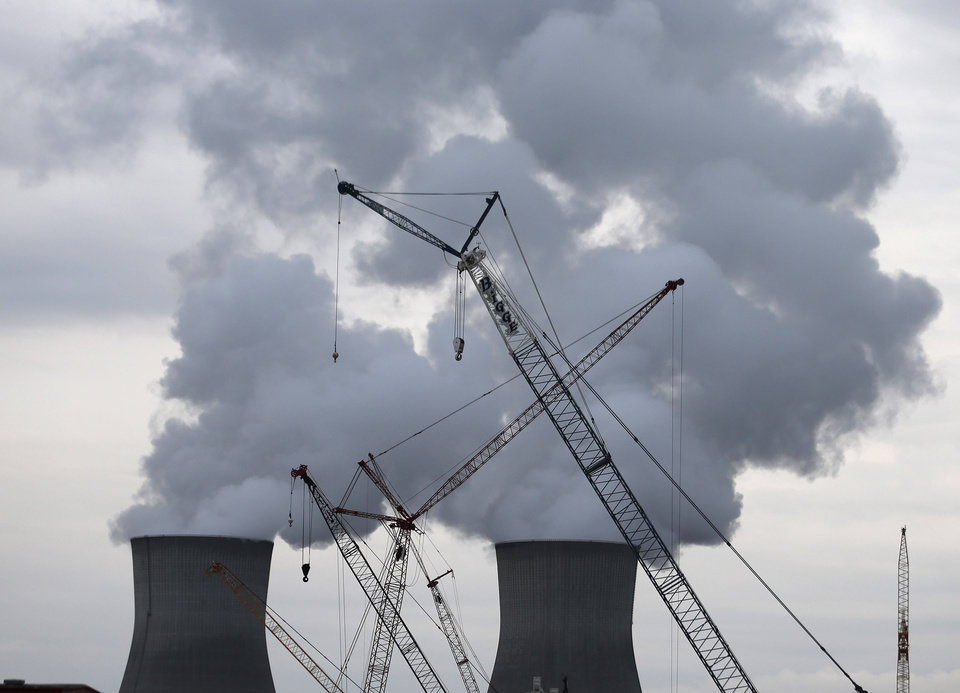 In this photo taken Monday, Dec. 11, 2012 Steam rises from the cooling towers at the Plant Vogtle nuclear power plant in Augusta, Ga., as cranes work to to build two new reactors. Atlanta-based Southern Co. planned to have the first of its new reactors at the plant built by April 1, 2016. A second reactor in eastern Georgia was supposed to come online the following year  but it could take at least a year longer than expected and involve hundreds of millions of dollars in extra costs. (AP Photo/John Bazemore)