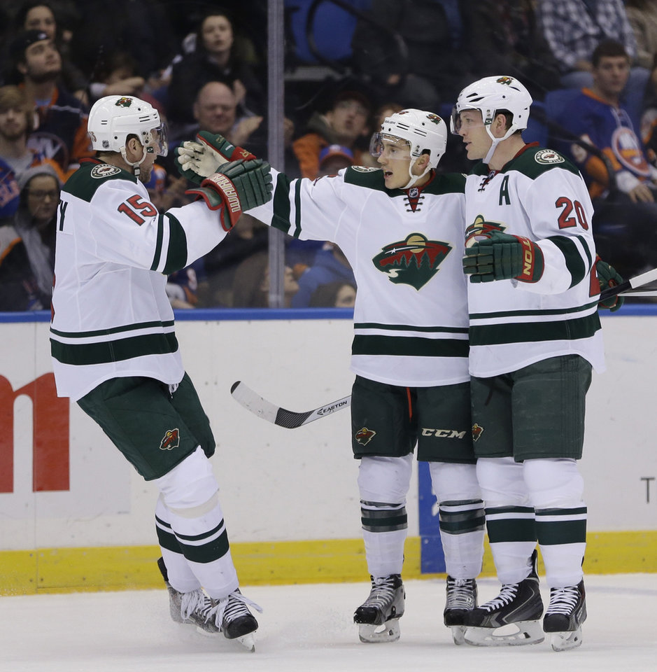 Photo - Minnesota Wild's Jared Spurgeon, center, celebrates his goal with teammates Dany Heatley, left, and Ryan Suter during the first period of the NHL hockey game against the New York Islanders, Tuesday, March 18, 2014, in Uniondale, New York. (AP Photo/Seth Wenig)