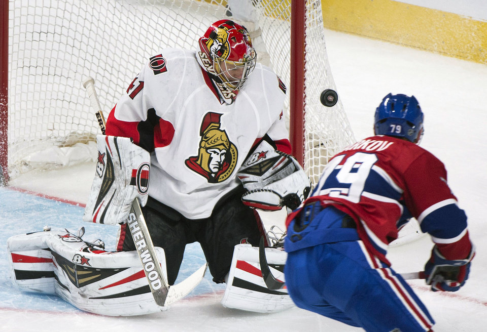 Photo - Ottawa Senators goaltender Craig Anderson, left, keeps an eye on the puck as Montreal Canadiens' Andrei Markov moves in during the second period of an NHL hockey game in Montreal, Saturday, Jan. 4, 2014. (AP Photo/The Canadian Press, Graham Hughes)