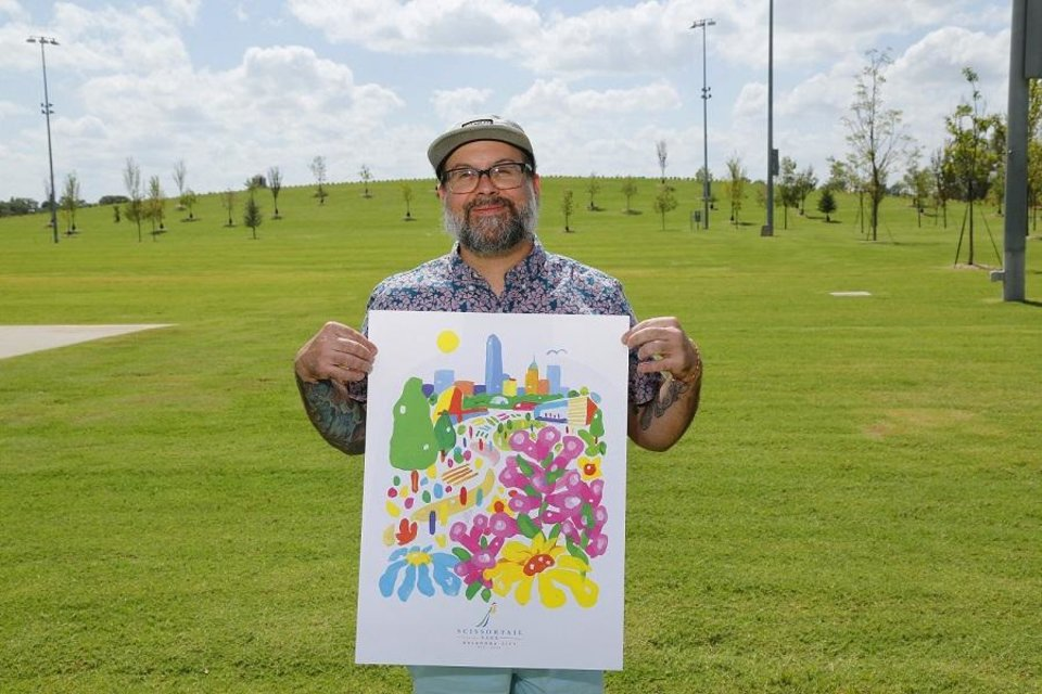 Photo -  Kris Kanaly holds a copy of the limited-edition poster he designed to mark the grand opening of Scissortail Park. [Photo by Doug Hoke]