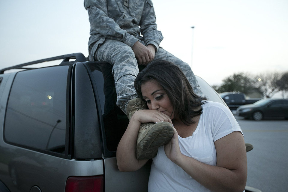 Photo - Lucy Hamlin leans on her husband's foot, Specialist Timothy Hamlin, as they wait to be allowed back onto Fort Hood, Texas, where they reside on Wednesday, April 2, 2014. A shooting occurred on the base with at least four dead and 14 injured according to the officials. (AP Photo/Austin American-Statesman, Deborah Cannon)