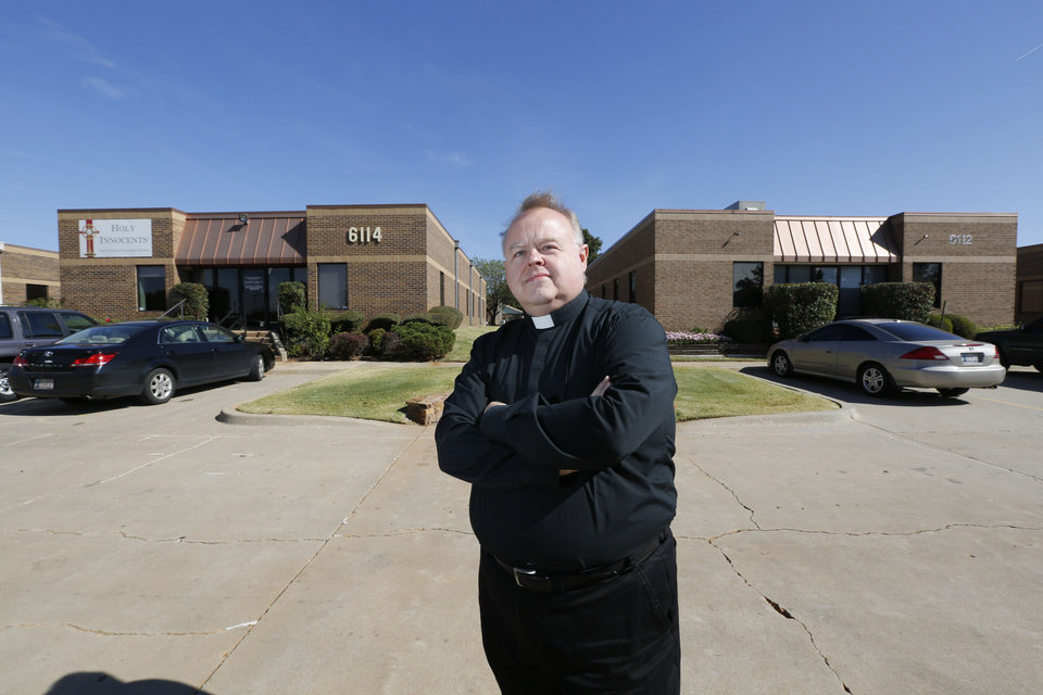 Photo - The Rev. Price Oswalt poses for a photo in front of the Holy Innocents Chapel in Warr Acres. The chapel, at back left, was built next door to the Outpatient Services for Women, an abortion clinic at back right.  Steve Gooch - The Oklahoman