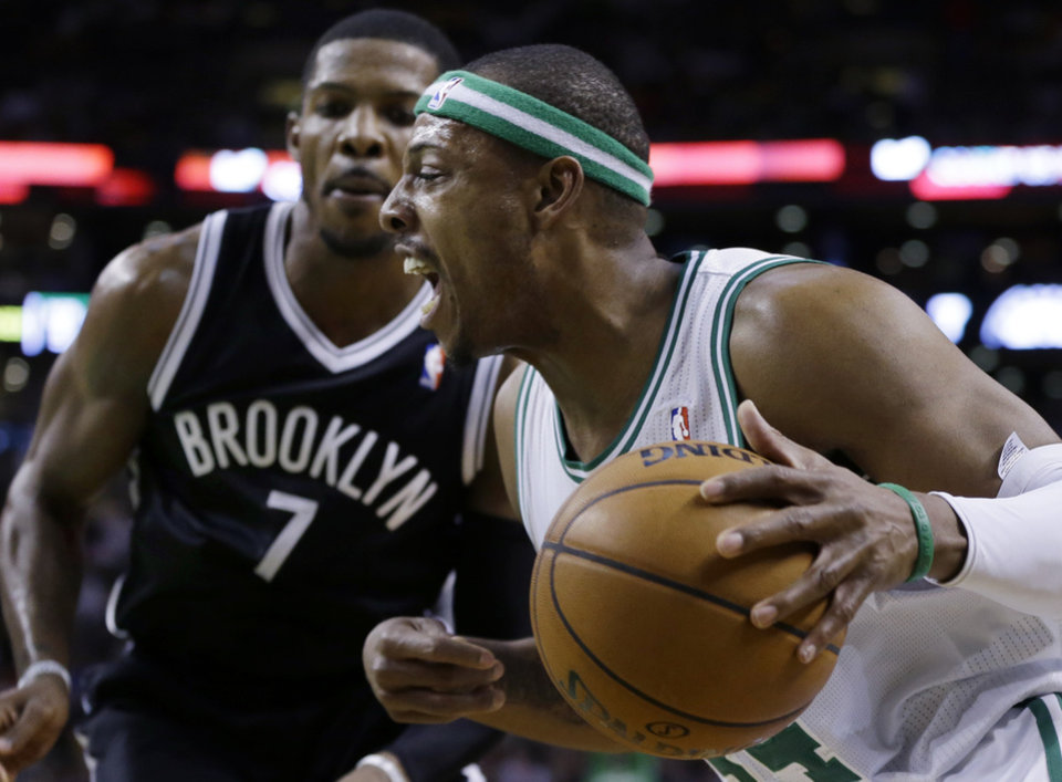 Photo - Boston Celtics forward Paul Pierce, right, drives past Brooklyn Nets guard Joe Johnson (7) during the first quarter of an NBA basketball game in Boston, Wednesday, April 10, 2013. (AP Photo/Elise Amendola)