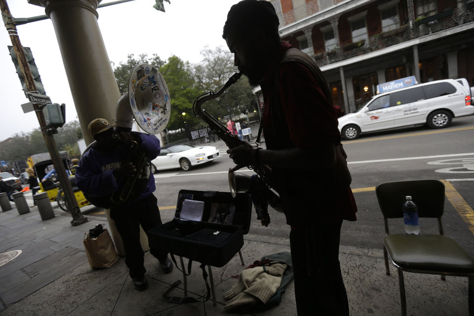 Photo - This Jan. 15, 2013 photo shows street musicians performing across the street from Jackson Square in New Orleans. Artists painting on canvas, clowns making balloon animals, street performers and jazz musicians are among the free entertainment to be found in Jackson Square, a one-block section of the French Quarter anchored by a lush green space with benches set among gardens and grand oak trees.   (AP Photo/Gerald Herbert)