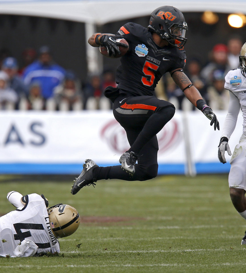 Photo - Oklahoma State's Josh Stewart (5) leaps past Purdue's Landon Feichter (44) during the Heart of Dallas Bowl football game between Oklahoma State University and Purdue University at the Cotton Bowl in Dallas, Tuesday, Jan. 1, 2013. Oklahoma State won 58-14. Photo by Bryan Terry, The Oklahoman