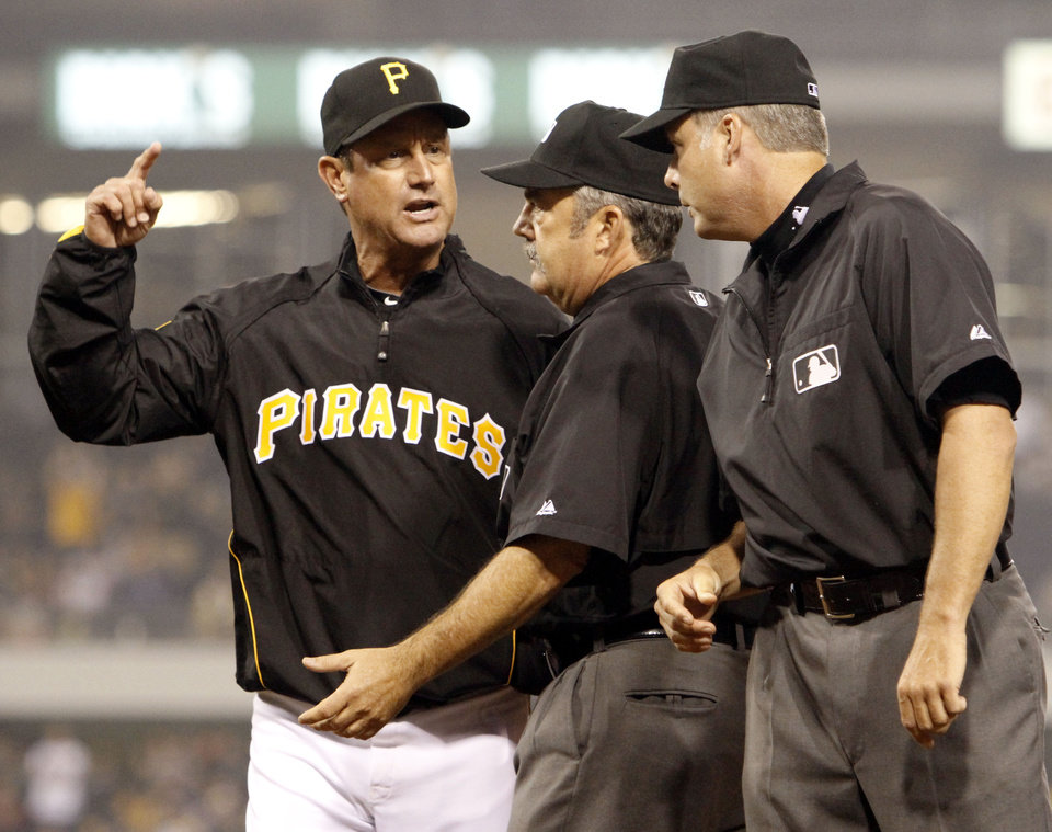 Photo - Second base umpire Tim Tschida, center, gets between Pittsburgh Pirates manager John Russell, left, and first base umpire Tim Timmons, right, after Timmons threw Russell out of the game after arguing a call safe at first that gave the Atlanta Braves a run in the ninth inning of the major league baseball game in Pittsburgh,  Saturday, May 22, 2010. The Braves won 4-2. (AP Photo/Keith Srakocic) ORG XMIT: PAKS110