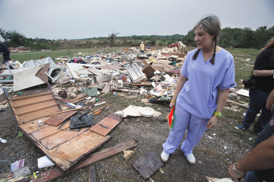 Photo - Ashley Walters helps her dad Olen Wells as they survey the damage to his mobile home after a tornado-spawning storm swept through the state on Tuesday, May 24, 2011, in Goldsby, Okla. Photo by Steve Sisney, The Oklahoman