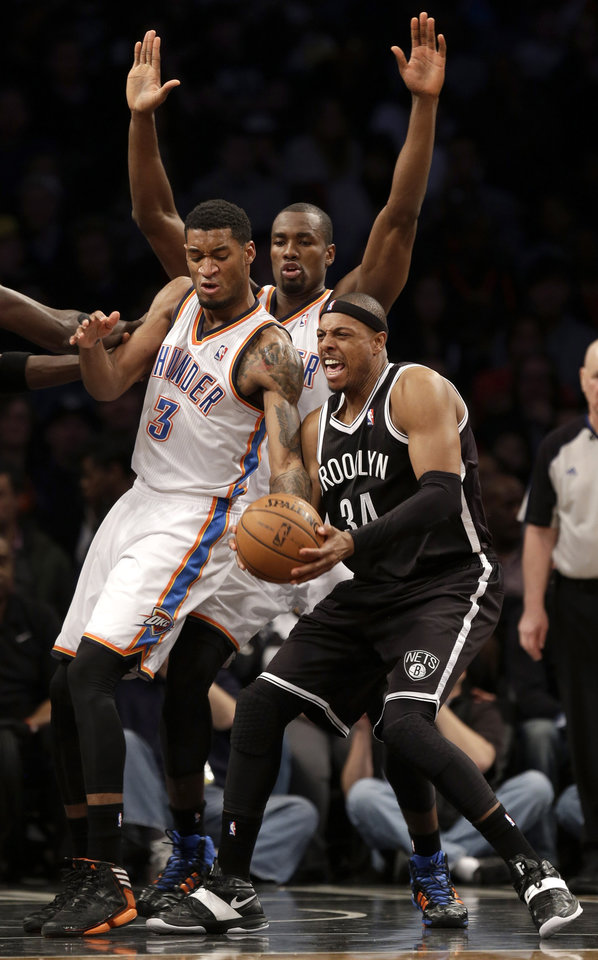 Photo - Brooklyn Nets' Paul Pierce, right, is fouled by Oklahoma City Thunder's Perry Jones, left, while Thunder's Serge Ibaka watches during the first half of an NBA basketball game Friday, Jan. 31, 2014, in New York. (AP Photo/Seth Wenig)